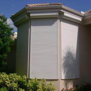 white roll down hurricane shutters on tan house