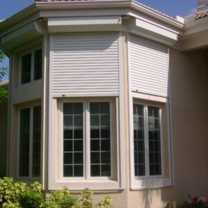 rolling shutters for windows on tan house