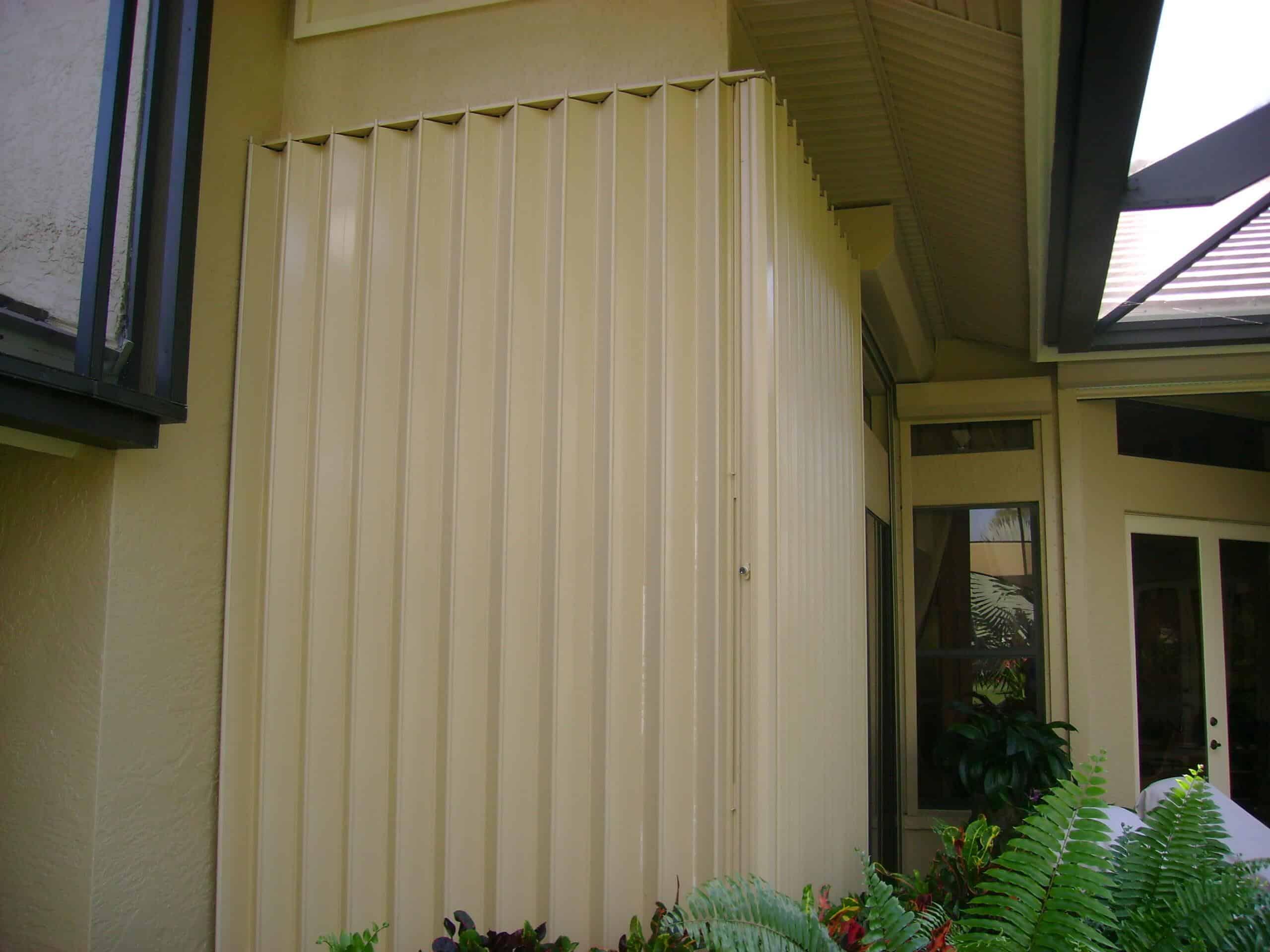 closed hurricane accordion shutters on house