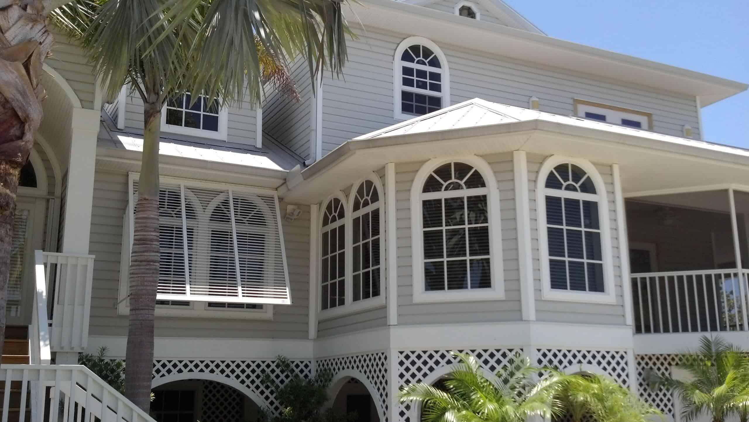open bahama hurricane shutters on tan house