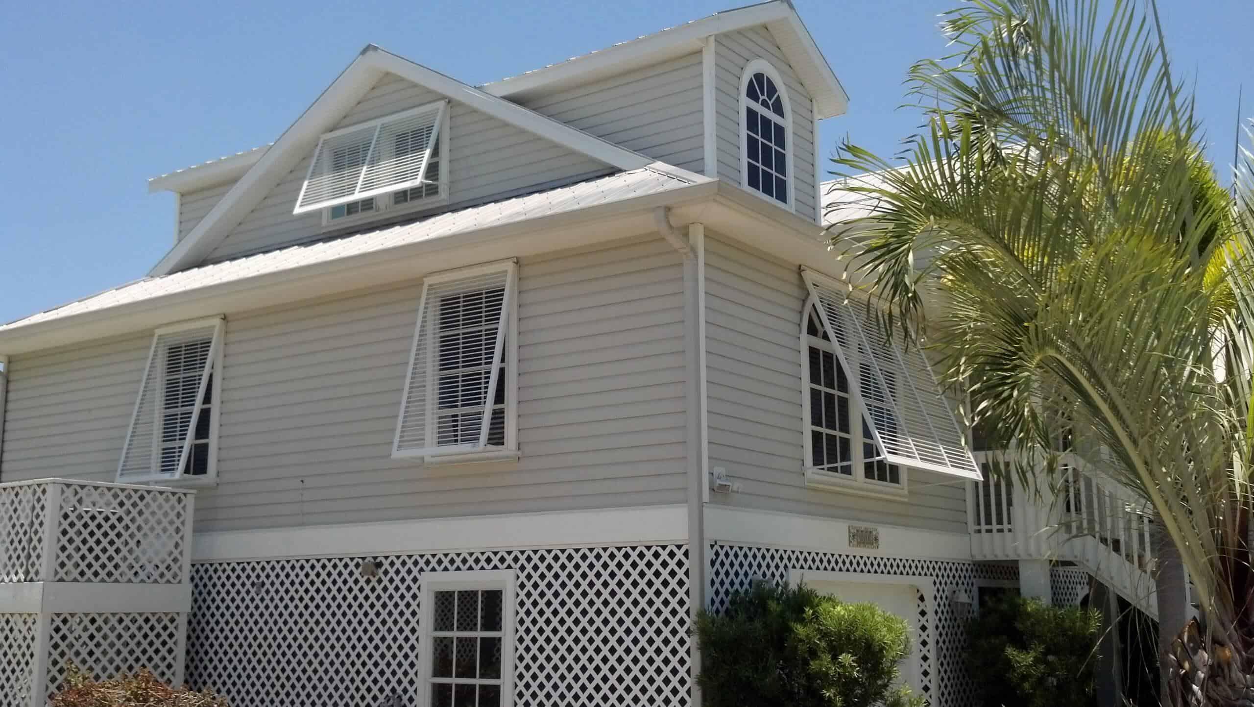bahama hurricane shutters on tan house