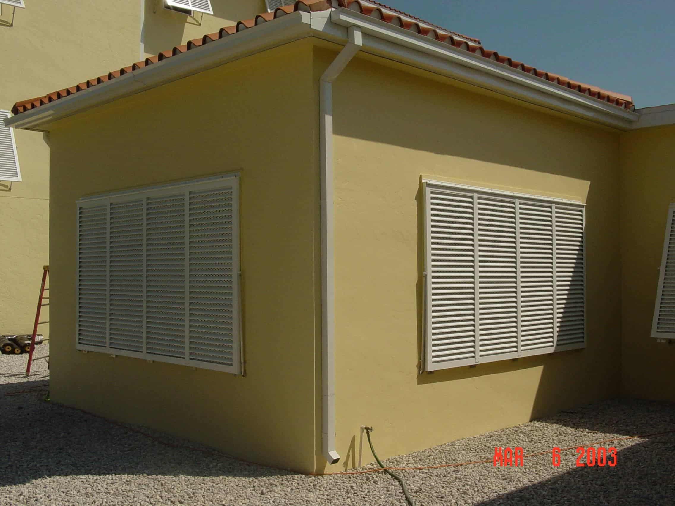 closed white bermuda shutters on yellow house