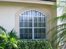tan house with clear window hurricane shutters