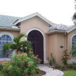 clear hurricane shutters on tan house